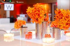 Monochromatic orange centerpiece with miracle roses and orchids.  Hammered silver vases, candles, and candy.  Illuminated table. Photo by Steve Krongard & Jodi Buren Photographers