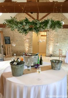 Getting the drinks reception area ready for the guests. A hanging floral 'circle' over the table with hanging tea light holders. A Wilde Bunch wedding design at Kingscote Barn Hanging Tea Light Holders, Hanging Lights, Barn Wedding Flowers, Wedding Day, Kingscote Barn, Reception Areas, Wedding Designs, Got Married, Big Day
