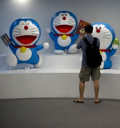 A visitor takes pictures a Doraemon statue during the 100 Doraemon Secret Gadgets Expo at a shopping mall in Kuala Lumpur. Malaysia is the first Southeast Asian country to host the expo displaying 100 life-sized Doraemon models with different gestures and facial expressions.