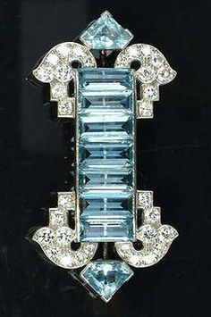 An Art Deco aquamarine and diamond brooch, by Cartier, circa 1935, set with a central line of seven uniform rectangular step-cut aquamarines, terminating with a scrolling brilliant-cut diamond spray to each corner and a single mitre-shaped aquamarine, signed Cartier London and numbered. #Cartier #ArtDeco #brooch