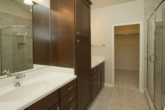 Ceramic tile flooring, custom ceramic shower with glass enclosure, solid surface counters, large linen cabinet, and a huge walk-in closet.
