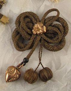 Victorian hair work in shape of a bow. The bow has a rose gold forget me not in the center. Dangling from the bow is a puffy rose gold heart and two round hair work balls.
