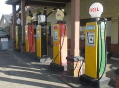 """An old garage forecourt with Avery Hardoll petrol pumps in Colyton, Devon, October 2014. See adjacent images of pump """"globe"""" details. The globes are probably reproductions."""