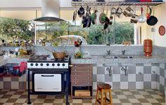 Já pensou cozinhar em um ambiente bem iluminado, com vista para a mata e todos os instrumentos à mão? Assim é o projeto do arquiteto Gustavo Penna. Os ladrilhos hidráulicos, inspirados na cidade de Tiradentes, cobrem o piso e sobem até a bancada