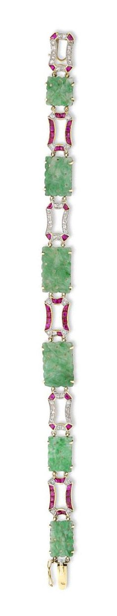 A 1920S JADE, RUBY AND DIAMOND PLAQUE BRACELET A fine Art Deco jade plaque bracelet, the bracelet comprising six rectangular plaques of ornately-carved jade or a floral design, alternately-set with modified rectangular ruby and diamond-set openwork links, all set in yellow gold, to a snap clasp with safety catch, gross weight 18 grams, measuring approximately 19 cm in length, circa 1920