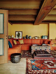 large orange sectional couch, aztec rugs, exposed rafters modern bohemian boho interior design / vintage and mod mix with nature, wood-tones and bright accent colors / anthropologie-inspired chic mid-century home decor