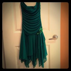 Dark Green Party Dress Strapless dark green dress, worn to a Christmas dance and a company formal. Very elegant and comfy. Green sequin flower on the left side no damage at all. Fits to figure on the top but the bottom flows out a little bit making it very comfy and fun to wear! Taboo Dresses