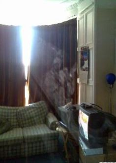 """Edinburgh Ghost Picture We received this ghost picture from Edward Nash of Edinburgh. We asked Ed if anyone was smoking. He responded, """"No, it's just dust in very bright sunlight!"""" How could dust form a figure we wonder??"""