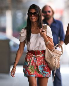 Kourtney Kardashian in a summery outfit, flowy top, cute skirt and the perfect round sunglasses!