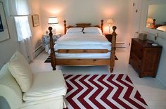 Bedroom with white walls, comforter and chair. Also includes bold red and white chevron throw rug.
