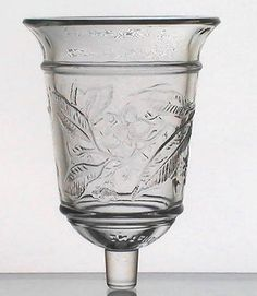 Home Interiors Peg Votive Cup Glass Magnolia Bell Brand: Home Interiors/Homco Height: 4.95 inches (including stem) Nearly 5 inches. Width: 3.5 inches Highly detailed raised relief design. Color: Clear Material: Glass Sample Photo No: 99