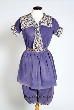 Swimming costume ca. 1910. Bathing dress in heavyweight blue satin cotton with false tie of blue & white print fabric on neck.All-in-one from shoulders to knees, and divided for the legs. V-neck with large sailor collar and short sleeves gathered into print cuffs with legs gathered into print bands. Separate short skirt with print waistband, which would be worn over the top, and gathers in back at waist level to allow for posterior. Walsall Museums via Black Country History