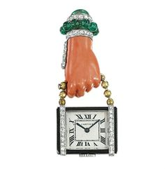 AN ART DECO PENDENT WATCH  The rectangular cream dial with Roman numerals and blued steel hands to the black enamel border and diamond sides, suspended from an associated carved coral hand with cabochon emerald and diamond surmount, with clip fitting, mechanical movement, circa 1930, 5.6 cm long, with French assay marks for gold on clip Dial signed Cartier, No. 08415, movement signed European Watch & Clock Co