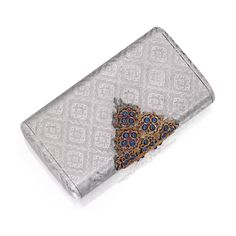 Silver, 18 Karat Gold, Sapphire and Ruby Evening Bag, Gianmaria Buccellati. The rectangular silver bag engraved in a brocade-like pattern, the clasp set with cabochon rubies and sapphires, the interior lined with suede.