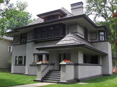 heavy window wills, front porch pointed roof, dark trim chimmney and corner features, wide roof overhang Frank Loyd Wright house in shades of grey. Love the design, but needs a balcony:)