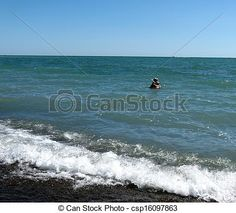 A woman in a blue sun hat, swimming in the ocean.