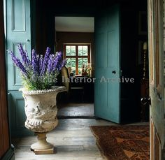 Delphiniums from the garden are arranged in an ancient urn on the floor of the hall