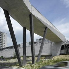 This faceted concrete footbridge spans a road in Lausanne, Switzerland, to connect a metro station with the scenic Sauvabelin Forest
