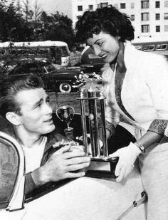 James Dean the Giant excepting a trophy while sitting in his racecar