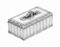 A RARE SILVER ART DECO CIGAR BOX MARK OF TIFFANY&CO.,NEW YORK, CIRCA 1940,DESIGN ATTRIBUTED TO ARTHUR L.BARNEY Rectangular,set on a series of narrow feet at the base,with columned sides,the hinged cover with a border of spirals and stylized trefoils,set with a central plaque of conforming decoration and surmounted by a reeded scroll finial, with wood-lined interior,the base engraved with presentation inscription,IRVING B. BABCOCK FROM PONTIAC FRIENDS, marked under base,also marked 22851Y…