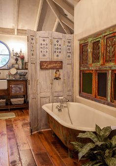 Rustic, exotic charm :: Salvaged tub, reclaimed shutter screen, & antique (dark green) stain glass window...