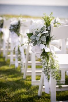 Pretty aisle decor flower arrangement - looks lie fern greenery, Lamb's Ear, white hydrangea and a white ribbon