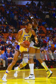 Kareem Abdul-Jabbar #33 of the Los Angeles Lakers drives pass Artis Gilmore #53 of the San Antonio Spurs during an NBA basketball game circa 1984 at The Forum in Inglewood, California. Abdul-Jabbar played for the Lakers from 1975-89.
