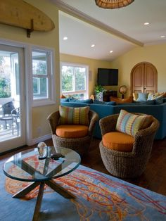 A relaxed coastal seating area in this home's family room provides a welcoming gathering spot. The ocean, sunset, and beachside location inspired the blue, yellow, and persimmon color scheme that is picked up in the custom accent pillows and Shivhon jellyfish rug.