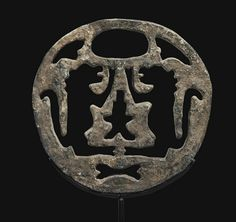 A BACTRIAN LEAD WEIGHT   CIRCA LATE 3RD-EARLY 2ND MILLENNIUM B.C.   Circular in form, the openwork design with two stylized, confronting rearing lions, surrounded by four symmetrical openwork forms, an oval perforation above serving as the handle  9½ in. (24.1 cm.) diameter