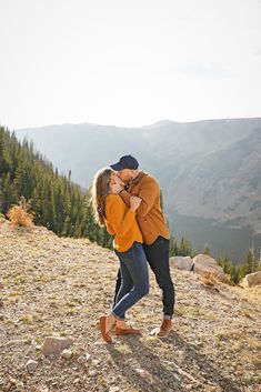 Fall Engagement Session - Red Lodge - Montana - Beartooth Pass - Beartooth Highway - Man - Woman - Engaged - Couple - Fiancé - Outdoor - Overlook - Mountains - Trees - Rocks - Brown - Gold - Orange - Sweater - Jacket - Jeans - Jeggings - Kissing - Blue Baseball Cap - Montana Wedding Photographer - Sara Nagel Photography