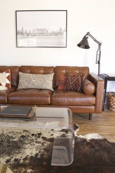 Masculine modern leather sofa, lucite coffee table, industrial lighting, African textile accents, and hide rug.