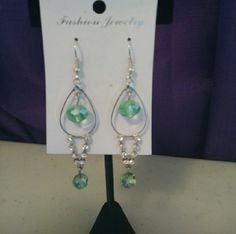 Silver dangly earrings with light green gems Brand new, never worn. Costume jewelry, not real silver. Beautiful for Spring and Summer. Pair with a cute maxi skirt or dress. Jewelry Earrings