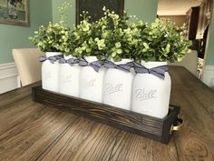This mason jar centerpiece unites modern farmhouse and rustic vintage wonderfully! It includes 5 white quart Mason jars, luscious greenery, and the box with gold handles.