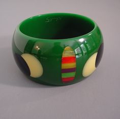 SHULTZ bakelite green chunky bangle with striped dots and overlapping cream and black dots, 2-1/2 by 1-5/8 by 1/3.