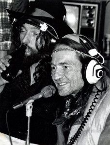 Waylon Jennings enjoying a beverage while doing a backstage radio interview with Willie Nelson. The interview took place during a break in performing at Charlie Daniel's Volunteer Jam in Nashville, TN.