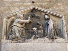 Soms heeft het naakte kindje zelfs een kruis op de schouders als voorafbeelding van zijn toekomstig lijden. Gezien de slechte staat van het bas-reliëf is niet duidelijk of het op deze voorstelling het geval is.   Ook de broeders van het hospitaal zijn - geknield en veel kleiner dan de heilige figuren van Maria en de engel - afgebeeld aan de voet van de bidstoel van Maria.