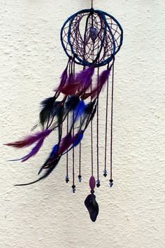 Purple and dark blue 3D dreamcatcher  A unique piece with original design  The yarn connect the three circles with the power of flow.  The diameter of the three circles is about 15cm . It has 35cm height . Purple, blue , blue black feathers and unique beads decorate the yarn sculpture. At the end of it, a seed is hanged. A seed of a rare and strange pumpkin that i have in my garden and i have colored in blue and purple shades. In the center of the dreamcatcher it has been placed a natural…