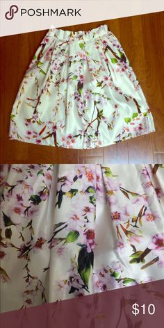 """White Sakura Print High Waist Pleated Midi Skirt Gorgeous skirt in the fit and flare style. Ivory background with a pink, green and brown floral pattern. Love this skirt, just at a loss with how to wear it. Waist measures 13"""" across but there is some room for stretch at the back of the waistband is elastic. Zipper closure on the side. Length of the skirt measures about 24"""". I could not find a tag for the material content, but I am guessing it is a polyester. The material is mid weight and it…"""