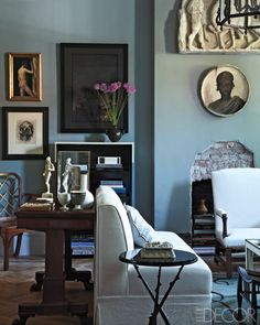 In the living room, the sofa is a custom design, the side table is by Hervé Van der Straeten, and the plaster frieze and portrait below it are 19th-century French; the walls are painted in Farrow & Ball's Pigeon.