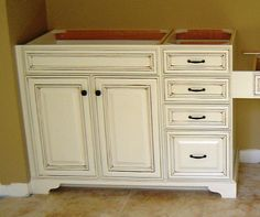 Add a furniture base to stock cabinets to make them look like real furniture. Could probably DIY this.