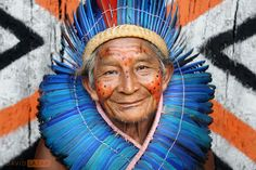 A portrait of the Chief of a village situated near the Amazon River. He wears traditional face paint, a full feather head dress, and his smile shows the warmth and happiness of the peaceful Dessana tribe.