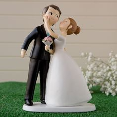 Cake topper o figura para pastel de boda. La novia besa al novio.