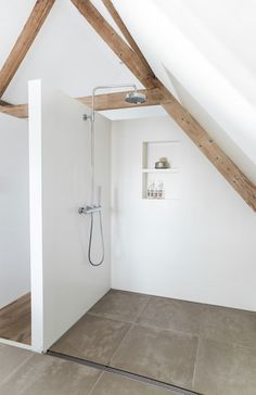 Minimalist shower situated below vaulted ceilings accented with exposed wood beams with wall mount shower kit boasting rain shower head and hand shower alongside recessed shelves over concrete floors finished with a linear shower drain.