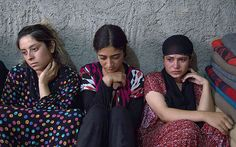 Yazidi regugees take shelter in an unfinished building in Dohuk