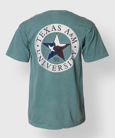"""This green comfort colors shirt has a tan circle on the back with blue text reading """"Texas A&M University"""". The star is filled with a Texas flag pattern. The front has a pocket with a Texas flag filled block ATM."""