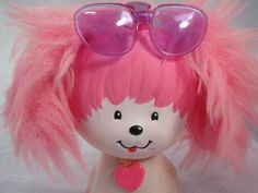 Poochie!!!! From Wikipedia: Poochie was a popular Mattel toy in the 1980s, a white poodle with pink ears and paws that wore a pair of purple sunglasses.[1] An animated special featuring the character was produced by DIC in 1984.