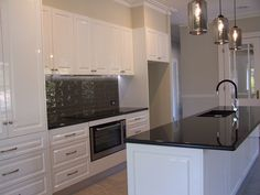 This kitchen features Jet Black Granite benchtops, with Polytec Vinyl Wrap, Casino Profile doors in Classic White gloss