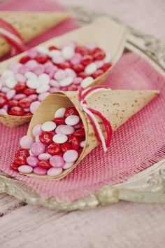 Clever idea for a Valentine's Day wedding favor: Use eco-friendly treat cones and fill them with red, pink and white M&Ms. Sweet and affordable!