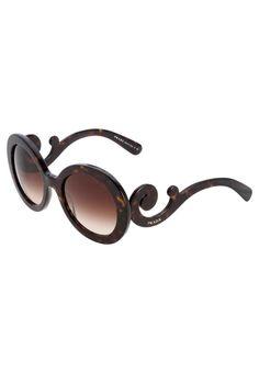 Wer es unkonventionell liebt, findet in dieser Sonnenbrille von Prada das perfekte Accessoire. Die ausladende Form und die geschwungenen Bügeln sind Ausdruck unwiderstehlicher Raffinesse. Diese Brille bricht mit dem modischen Mainstream und gibt eine ganz eigene Richtung vor, der du als modeaffine Frau nur zu gerne folgst.