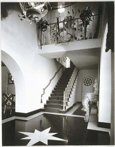 """Elsie De Wolfe's Beverly Hills Home """"AFTER ALL"""" :The entrance hall at """"After All"""" which Tony Duquette decorated in black and white with a fantasy singer's balcony hung with fishnet and seashells, and a mermaid.  Note the original Tony Duquette lantern hanging form the ceiling."""